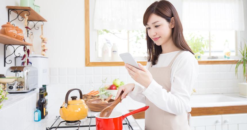 梅干しを使った料理のレシピを調べている女性の写真